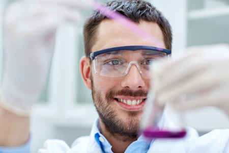 science, chemistry, technology, biology and people concept - young scientist mixing reagents from glass flasks and making test or research in clinical laboratory Stock Photo