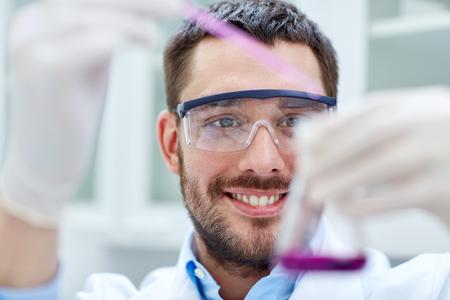 wetenschap, chemie, technologie, biologie en mensen concept - jonge wetenschapper het mengen van reagentia uit glazen flessen en het maken van testen of onderzoek in klinisch laboratorium