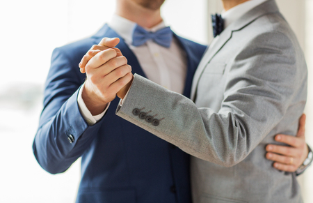 people, homosexuality, same-sex marriage and love concept - close up of happy male gay couple holding hands and dancing on wedding Stock Photo