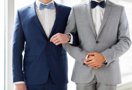 same sex: people, homosexuality, same-sex marriage and love concept - close up of happy male gay couple holding hands on wedding Stock Photo
