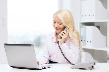 education, business, communication and technology concept - smiling businesswoman or student with laptop computer calling on phone in office Standard-Bild