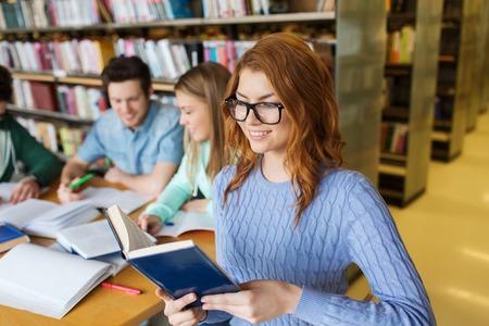 estudiantes universitarios: las personas, el conocimiento, la educación, la literatura y la escuela concepto - mujer joven feliz en gafas de leer el libro y se preparan para los exámenes sobre el grupo de estudiantes en la biblioteca