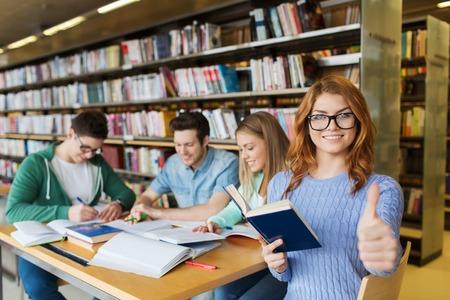 mensen, kennis, onderwijs, gebaar en school concept - gelukkige student meisje zien thumbs up in de bibliotheek Stockfoto