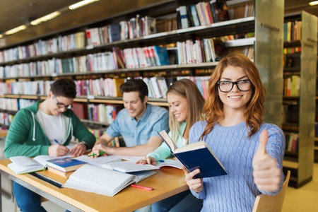 people, knowledge, education, gesture and school concept - happy student girl showing thumbs up in library Stock Photo