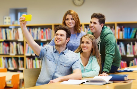books library: people, technology, friendship, education and school concept - group of happy students with smartphone taking selfie at library Stock Photo