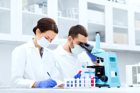 farmacia: ciencia, química, la tecnología, la biología y la gente concepto - jóvenes científicos con tubo de ensayo y microscopio haciendo investigación en laboratorio clínico y tomar notas