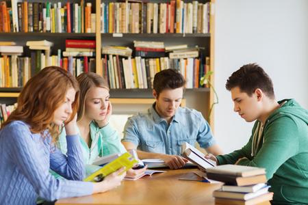 personas leyendo: las personas, el conocimiento, la educación y la escuela concepto - grupo de estudiantes de la lectura de libros y se preparan para el examen en la biblioteca