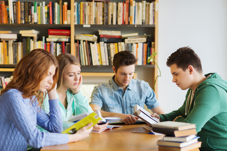mensen, kennis, onderwijs en school concept - groep studenten het lezen van boeken en het voorbereiden om examen in de bibliotheek