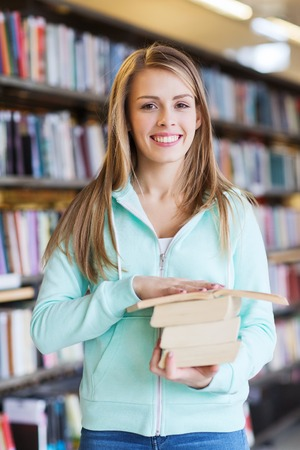 happy teenager: people, knowledge, education and school concept - happy student girl or young woman with book in library