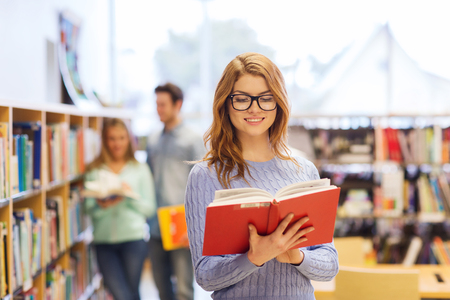 woman  glasses: people, knowledge, education and school concept - happy student girl or young woman with book in library