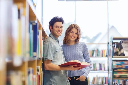 estudiantes universitarios: las personas, el conocimiento, la educación y la escuela concepto - pareja feliz estudiante con libros en la biblioteca Foto de archivo