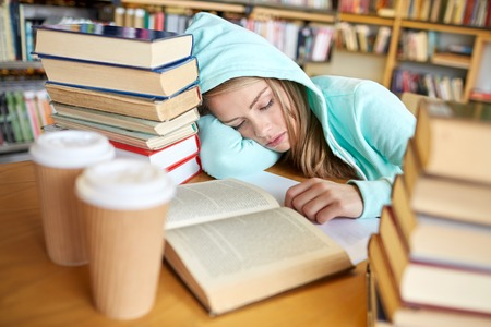 student in library: people, education, session, exams and school concept - tired student girl or young woman with books and coffee sleeping in library Stock Photo