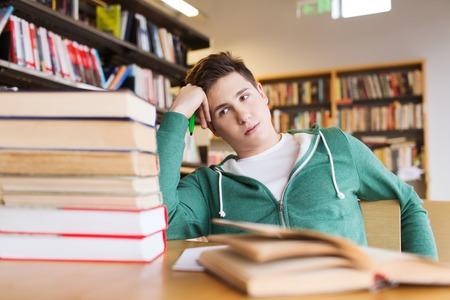 adolescentes estudiando: las personas, el conocimiento, la educación, la literatura y el concepto de la escuela - estudiante aburrido o joven con los libros en la biblioteca de soñar