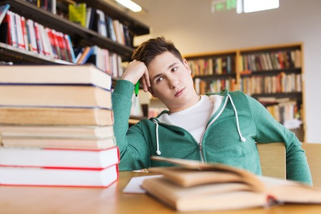 people, knowledge, education, literature and school concept - bored student or young man with books dreaming in library Standard-Bild