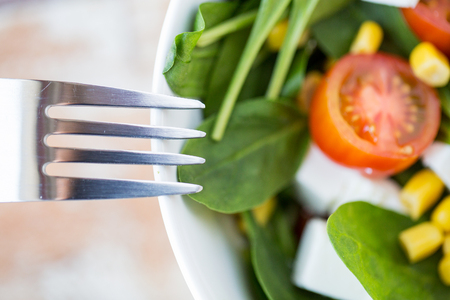 eating salad: healthy eating, dieting, vegetarian kitchen and cooking concept - close up of vegetable salad bowl and fork at home