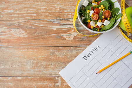 meal: healthy eating, dieting, slimming and weigh loss concept - close up of diet plan paper green apple, measuring tape and salad Stock Photo