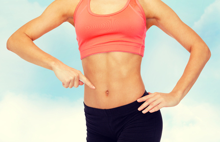 shaping: fitness, exercise and diet concept - close up of woman pointing finger at her six pack Stock Photo
