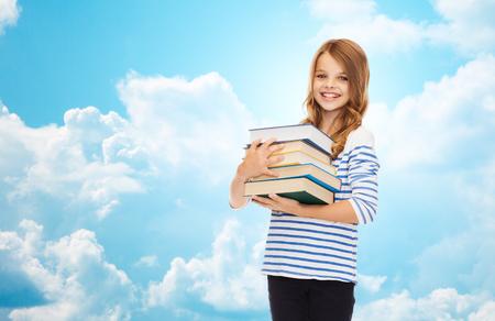L'éducation, les gens, les enfants et les concept de l'école - petite fille heureuse d'étudiant avec de nombreux livres sur le ciel bleu avec des nuages ??de fond Banque d'images - 46993198
