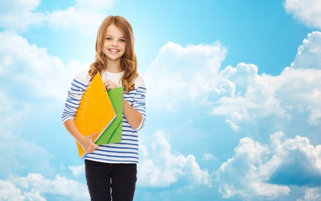 cute teen: education, people, children and school concept - happy girl holding colorful folders over blue sky with clouds background