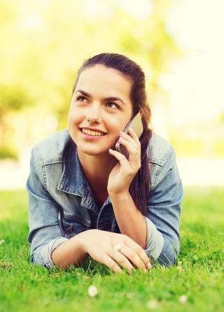 hablando por telefono: estilo de vida, vacaciones de verano, la tecnología, el ocio y el concepto de la gente - sonriente joven con el teléfono inteligente hablar y tumbado en la hierba en el parque Foto de archivo