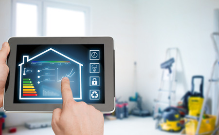 energy consumption: home, housing, people and technology concept - close up of man hands pointing finger to tablet pc computer and regulating room temperature over storeroom or building background