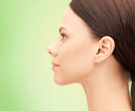 profile: health, people and beauty concept - beautiful young woman face over green background