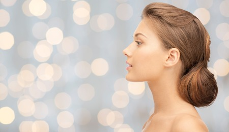 health, people, holidays, luxury and beauty concept - beautiful young woman face over lights background Stock Photo