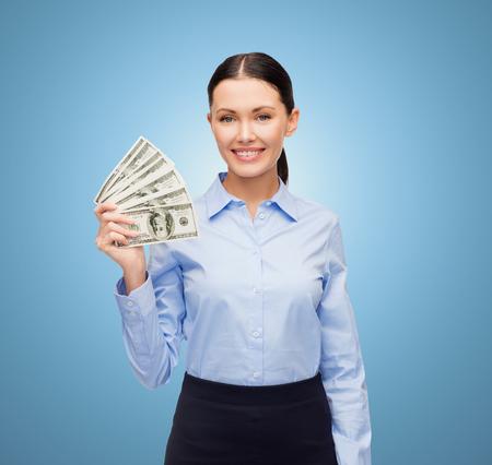 cash money: negocio y dinero concepto - joven empresaria con el dinero d�lares en efectivo sobre fondo azul
