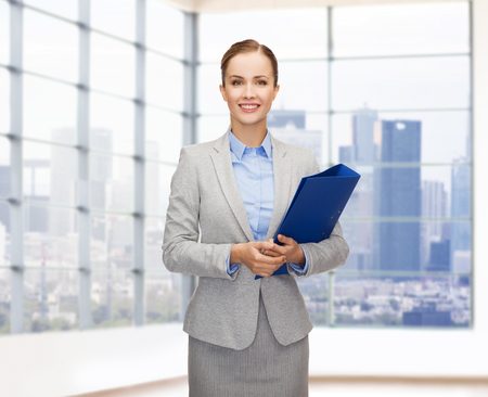 real business: business, people, real estate and sale concept - smiling young businesswoman holding folder over office or empty city apartment background