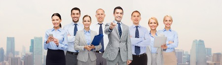 group of business people: business, people, corporate, teamwork and office concept - group of happy businesspeople pointing at you over city background Stock Photo