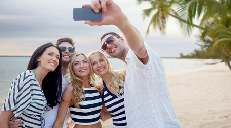 the girl is young: summer, sea, tourism, technology and people concept - group of smiling friends with smartphone photographing and taking selfie on beach