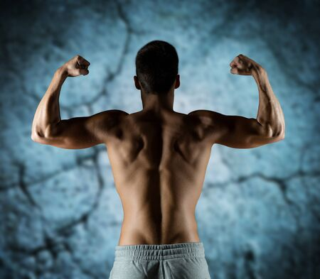 man gym: sport, fitness, bodybuilding, strength and people concept - young man or bodybuilder showing biceps over concrete wall background from back Stock Photo