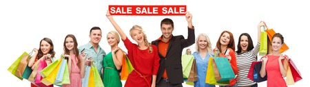 sale sign: consumerism, people and discount concept - group of happy people with sale sign and shopping bags Stock Photo
