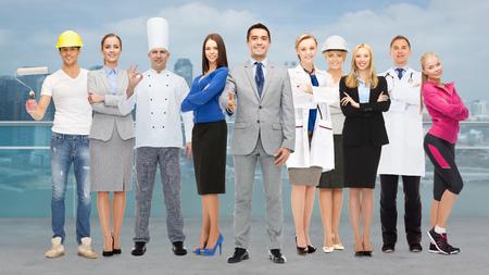 ouvrier: les gens, de la profession, de la qualification, de l'emploi et le concept de succès - d'affaires heureux avec un groupe de travailleurs professionnels montrant thumbs up sur la ville de fond Banque d'images