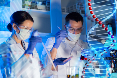 science, chemistry, biology, medicine and people concept - close up of young scientists with pipette and flasks making test or research in clinical laboratory over dna molecule structure
