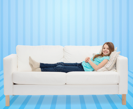 girl lying: home, leisure, people and happiness concept - smiling little girl lying on sofa over blue striped background