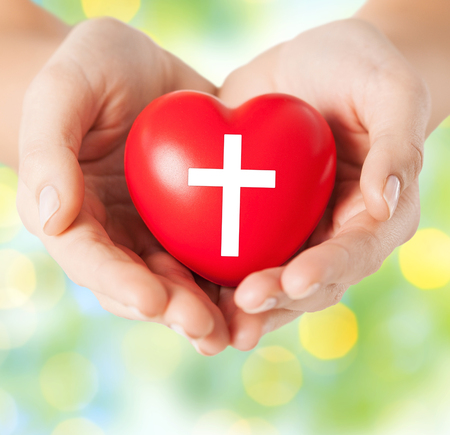 christian community: religion, christianity and charity concept - close up of female hands holding red heart with christian cross symbol over green lights background