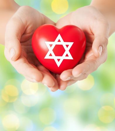Concepto de religión, cristianismo, la comunidad judía y de la caridad - cerca de las manos femeninas celebración de corazón rojo con la estrella de david símbolo sobre luces de fondo verde Foto de archivo - 46993264