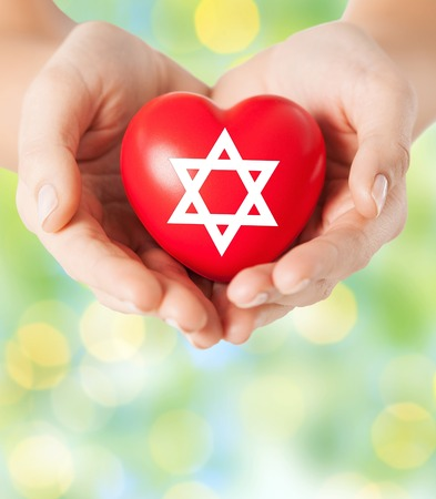 jewish star: religion, christianity, jewish community and charity concept - close up of female hands holding red heart with star of david symbol over green lights background Stock Photo