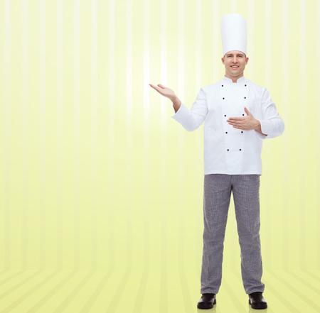 invitando: la cocina, la profesión y el concepto de la gente - cocinero de sexo masculino feliz cocinar invitando sobre fondo amarillo Foto de archivo