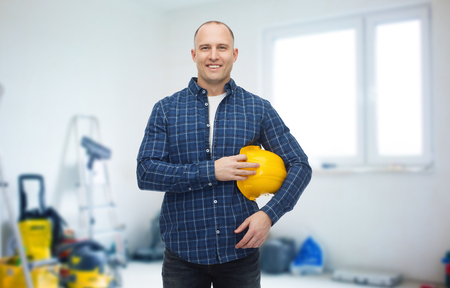 storeroom: repair, building, construction and maintenance concept - smiling man holding helmet over storeroom background Stock Photo