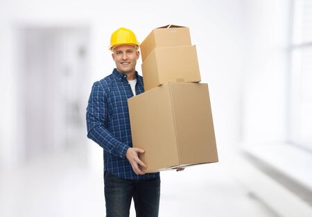 delivery room: repair, building, construction, loading and delivery concept - smiling man or loader in helmet with cardboard boxes over room background