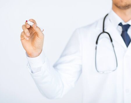 close up of doctor writing something in the air with marker Stock Photo