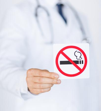 hombre fumando: cerca de la explotación agrícola del doctor señal de no fumar en las manos