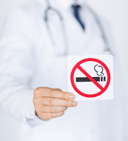 no smoking: close up of doctor holding no smoking sign in hands