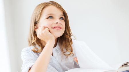 jolie petite fille: l'�ducation et l'�cole notion - petite fille �tudiante �crit dans le cahier � l'�cole