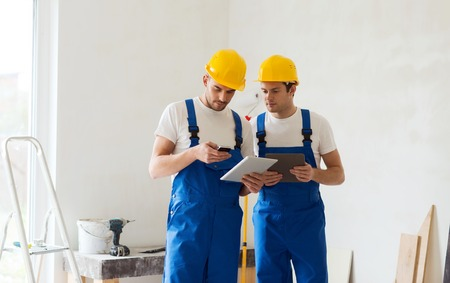 de bouw, renovatie, technologie, elektriciteit en mensen concept - twee bouwers met tablet pc computer en smartphone binnenshuis