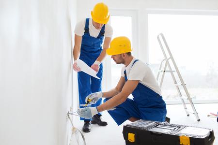 building: la construcción, renovación, la tecnología, la electricidad y el concepto de la gente - dos constructores con ordenador Tablet PC que trabajan con el interior de la electricidad