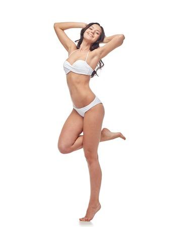 belles jambes: les gens, la mode, maillots de bain, l'été et le concept de plage - heureux jeune femme posant en bikini blanc maillot de bain avec les mains levées et debout sur une jambe