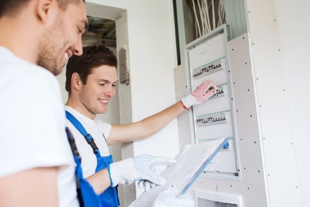 work gloves: business, building, teamwork and people concept - group of smiling builders with clipboard and electrical panel indoors Stock Photo